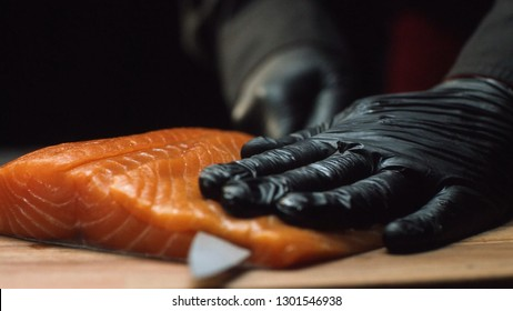 Close-up chef with piece of red salmon. Professional chef in black gloves holds piece of fresh salmon and is ready to cut it