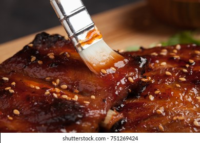 Close-up chef spreading sauce bbq on ribs with brush.
