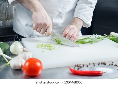 Closeup chef's hands cooking green onion for preparing healthy vegetable salad on cutting board in restaurant kitchen. Concept new lean menu, low calories speciality