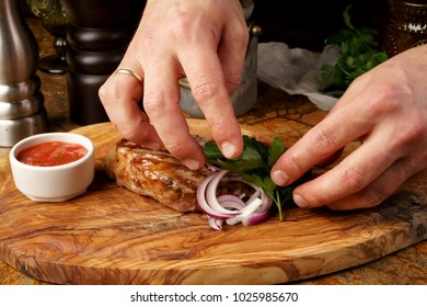 Closeup of chef's hands decorating meat steak with basil leaves.