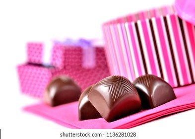 Close-up of cherry chocolate with a creamy filling liquor and pink romantic gift box on white background