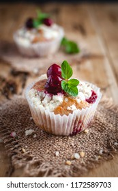Close-up of cherry muffin with crumbly topping on wooden background