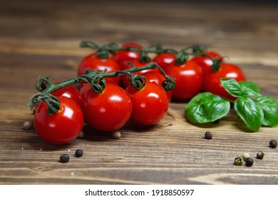 Closeup cherry tomatoes and basil and pepper on rustic background - fresh cherry tomatoes on wooden table, horizontal orientation.