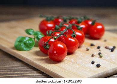 Closeup of cherry tomatoes and basil and pepper a cutting board on rustic background - fresh cherry tomatoes on wooden table, horizontal orientation.
