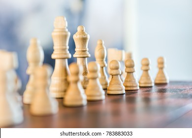 Closeup of chessboard with wooden pieces on table in sunlight, soft bokeh
