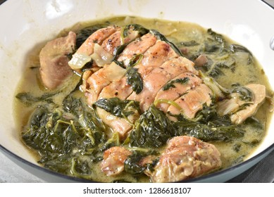 Closeup of chicken florentine in a skillet, high angle view