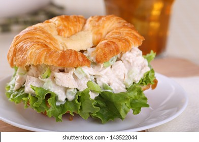 Closeup of a chicken salad and lettuce sandwich on a croissant roll with a drink in background