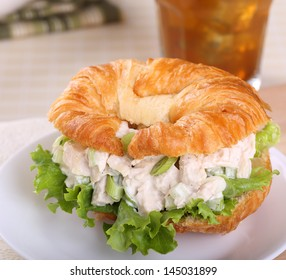 Closeup of a chicken salad with lettuce sandwich on a croissant roll