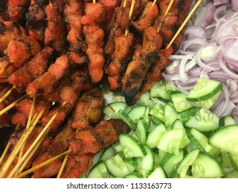 Closeup of chicken satay with cucumber and onion slices