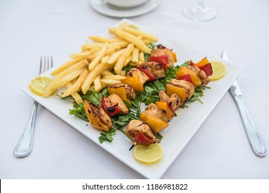 Closeup of chicken shish tawook kebab meal on plate in outdoor luxury restaurant setting