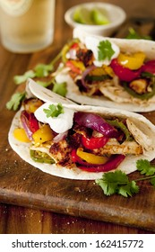 Closeup of chicken and vegetable fajitas with a dollop of sour cream.