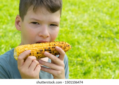 close-up, child boy, eating baked corn on the cob, against a background of green grass, there is a place for inscription