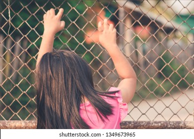 Closeup Child girl holding steel fence. Rear view.Concept for child abuse, human trafficking, crime and domestic violence,protection of kid.