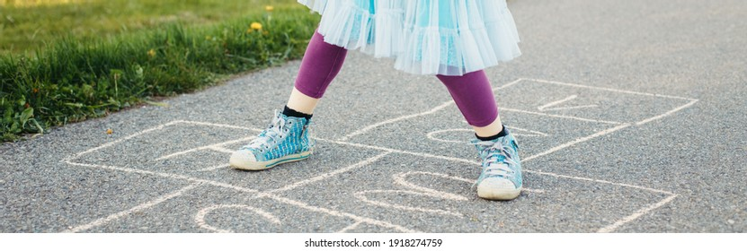 Closeup of child girl playing jumping hopscotch outdoor. Funny activity game for kids on playground. Summer backyard street sport for children. Happy childhood lifestyle. Web banner header.