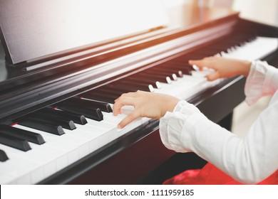 Closeup child hand playing piano.