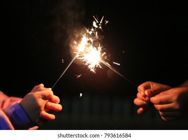Close-up child hands holding fire sparklers on the festival.