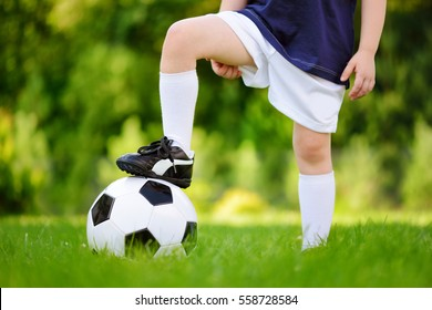 Close-up of a child having fun playing a soccer game on sunny summer day. Sport activities for children. Kids in sports uniform.