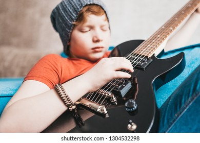 Closeup of a child playing a black electric guitar - hand picks up the notes on the strings - selective focus