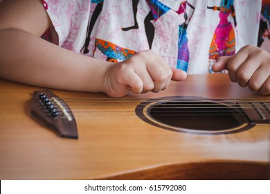 Close-up child playing guitar. Concept of liftstyle, learning, hobby, musician, dream and imagination.
