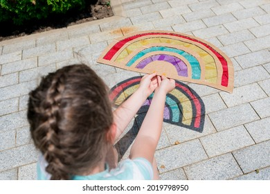 Close-up of child s hand holding a rainbow craft suncatcher. Summer fun activities for the development of fine motor skills. Shadow art with recyclable materials with kids.