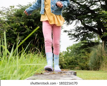 Closeup of a child wearing wellies walking towards the cameral in a garden. Girl hiking in a park. Exploring nature. - Shutterstock ID 1832216170
