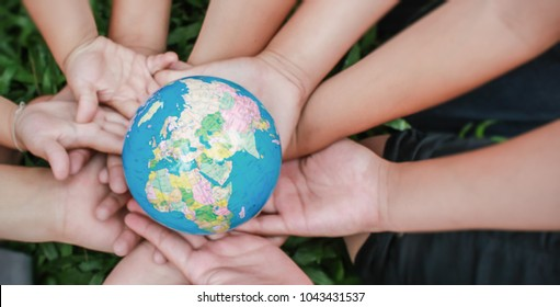 Closeup children hands holding earth ( blur ) over green grass background. World harmony green peace environment spring and earth day together concept panorama banner