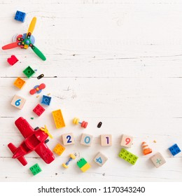 Closeup of children multi-color plastic bricks with wooden cubes figures 2019 on white wooden background. Early learning. Developing toys