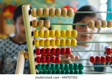 Closeup of children working with abacus in the classroom