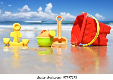 Closeup of children's beach toys at the beach - focus on the watering can