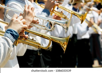 Closeup of children's brass band. Children play on golden pipes. The concept of lifestyle and youth culture.