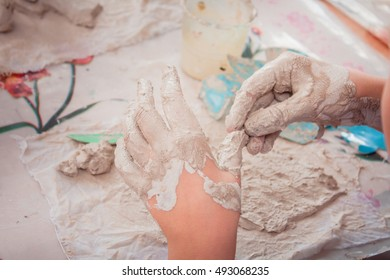 Closeup of children's dirty hands in clay; art therapy