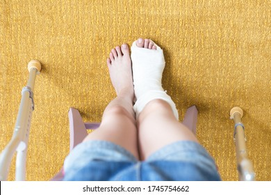 Close-up of children's feet, one leg is broken and in a cast, next to crutches. Yellow background. Top view.