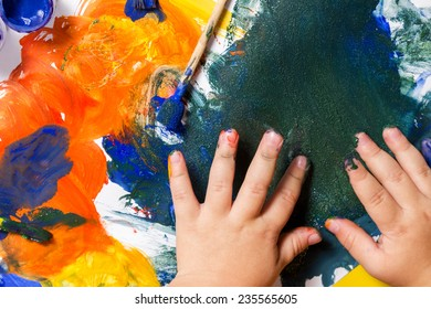 Closeup childrens hands painted with a brush on paper