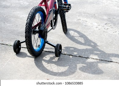 closeup of a child's first bike, with training wheels