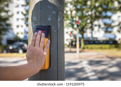 Close-up of a child's hand on the capacitive push button of a pedestrian traffic light