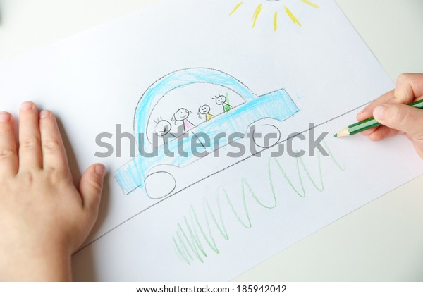 Close-up of childs hands drawing a blue car with a family in it