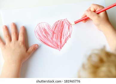 Close-up of childs hands drawing a red heart