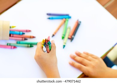 Closeup of child's hands with lots of colorful wax crayons pencils. Kid preparing stationary and student stuff. Back to school concept