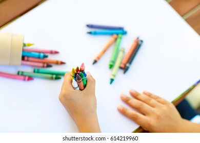 Close-up of child's hands with lots of colorful wax crayons pencils. Kid preparing school and nursery equipment and student stuff. Back to school. Education, school, learning concept.