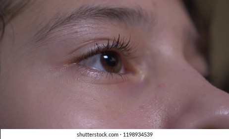 Close-up of a child's human eye. the girl looks closely at the TV screen while watching the video