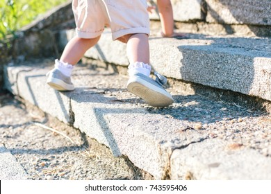 Closeup of child's legs climbing on stairs