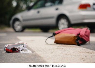 Close-up of child's shoe and knapsack on a pedestrian crossing after a collision with a car
