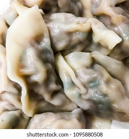 Closeup of Chinese boiled pork and chive dumplings - background or texture