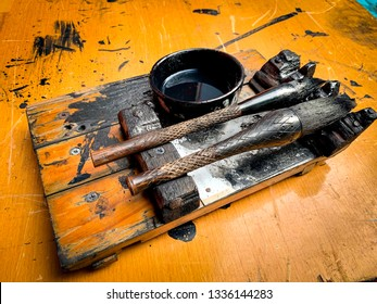 Close-up of Chinese Calligraphy brushes and ink on wooden brush shelf on writing table