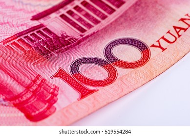 "Closeup of Chinese hundred RMB yuan note, focusing on text ""100 YUAN"", on white background"