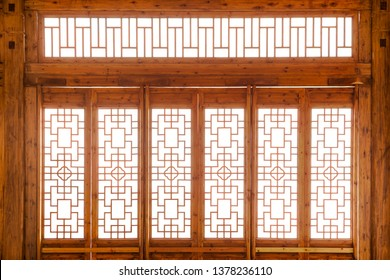 Closeup Chinese old wooden frame door with decorative pattern under the sunshine ,view from inside of building.