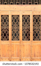 Closeup Chinese old wooden frame door with decorative pattern under the sunshine ,view from outside of building.
