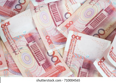 Closeup Chinese yuan bills on table. Yuan is the currency of China, Selective focus on stack of one hundred Chinese yuan banknotes for money background in tone.