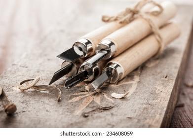 closeup chisels for wood on carpenter desktop