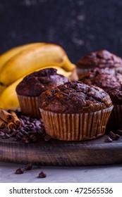 Closeup of chocolate banana muffins with cinnamon on the wooden board. Dark photo.